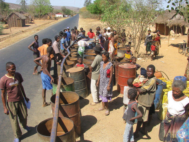 Filling barrels with water brought by a lorry of the Mission